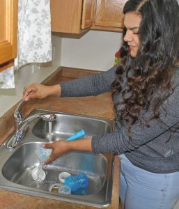 Cristal Aguirre Anchondo uses hot water to wash up a bottle for her infant son Jonathan. The single mother has a working hot water system in her Rifle home after three months of making do.
